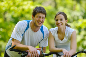 Happy couple riding bicycle outdoors, health lifestyle fun love romance concept