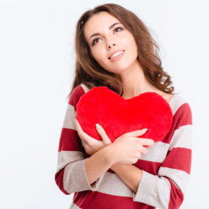 Portrait of a happy thoughtful woman holding red heart and looking up isolated on a white background